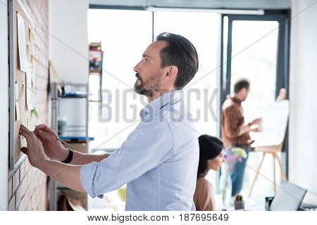 Concentrated manager is holding pencil and looking at board. Colleagues are absorbedly working in room. Profile