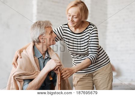 Love cures everything. Nice sweet elderly woman making sure her man feeling comfortable and warm while providing him a blanket and hugging him a little