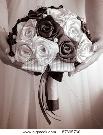 The bride's bouquet in hands on background of the wedding dress in monochrome tones