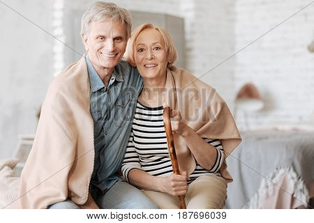 Never apart. Radiant positive senior people sitting in the bedroom and hugging while wrapping themselves in a cozy blanket