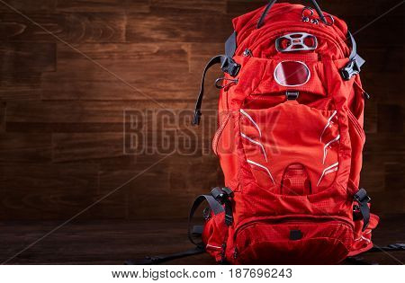 Close-up of the big hiking orange backpack against wooden background. Horizontal photo of the tourism rucksack. Tourism backgrounds and still-life. Preparation and planning for the travelling. Concept of the active lifestyle.