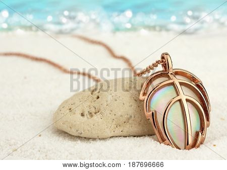 Golden jewellery pendant on summer sand beach with sea background soft focus