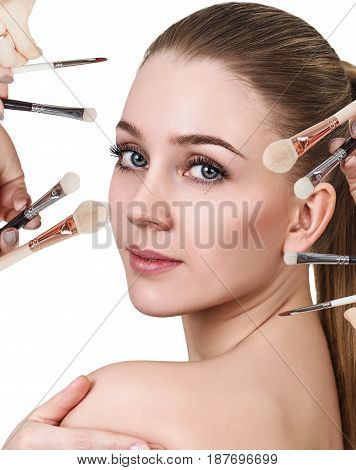 Hands with cosmetics brushes doing make-up to young woman, over white background