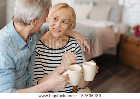 Lifelong friends. Gallant caring elderly man serving his lady warm drink and chatting with her about everything while enjoying their time together