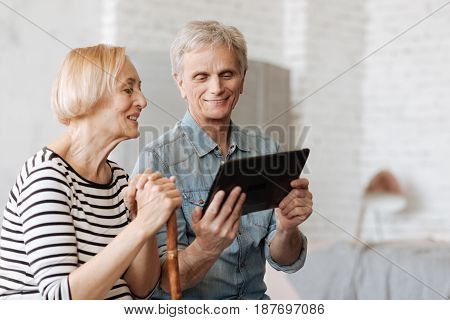 Engaging experience. Savvy intelligent senior gentleman using his gadget for demonstrating an interesting article he reading online
