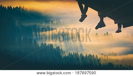 Hikers sit on a wooden flooring above the carpathian mountain valley covered with golden morning fog. Instagram stylisation.