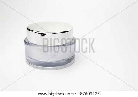 white and silver cosmetic jar on a white background