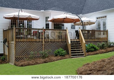Backyard Wood Deck Patio With Umbrellas And Furniture
