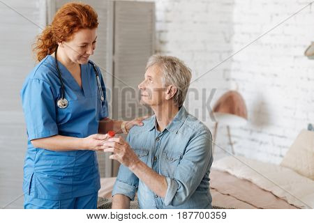 Thank you for helping me. Delicate trained professional woman taking care of elderly gentleman while paying him a visit and bringing needed medication