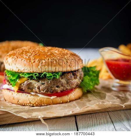 American hamburger with beef, french fries and tomato sauce on dark background.