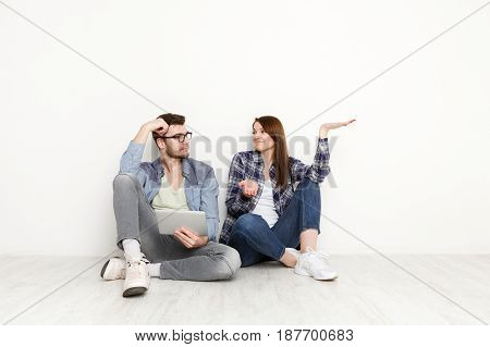 Wasting money for shopping. Couple at home sitting on floor and using digital gadget together, white background