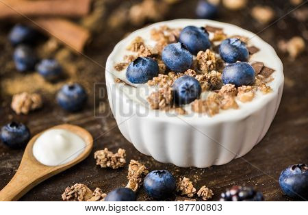 Serving of Yogurt with Whole Fresh Blueberries and Muesli on Old Rustic Wooden Table. Closeup Detail.