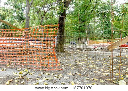 Confined space with orange plastic safety net is placed around the building site in deciduous park.