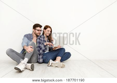 Couple conversation with laptop. Man showing project to woman on laptop computer, white background, studio shot