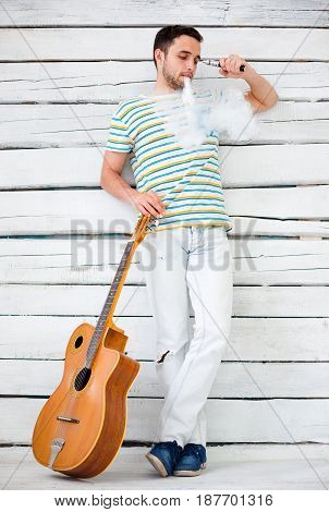The face of vaping young man on black studio background with guitar