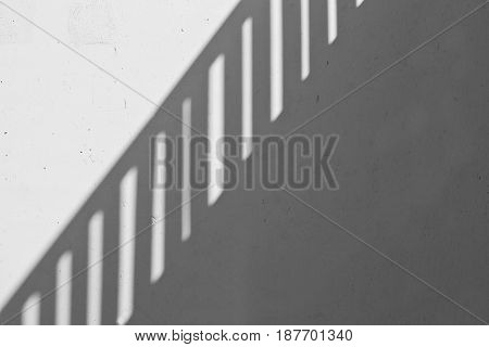 abstract view of a steel banister reflected on a wall in full sunshine