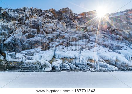 Frozen rock island with icicles in Lake Baikal Russia