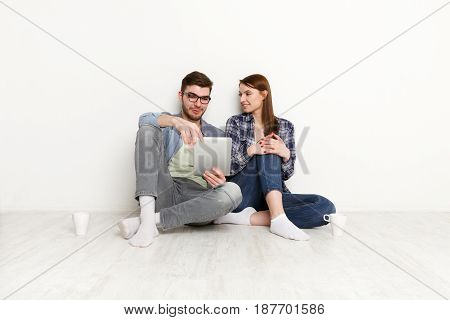 Couple choosing goods online, sitting on floor in empty apartment on white background