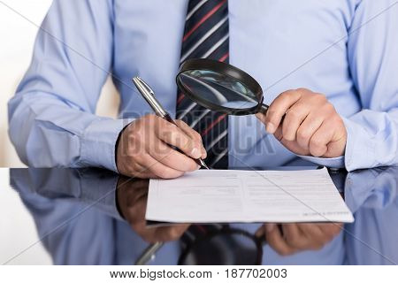 Businessman examines the contract with the magnifying glass before signing it