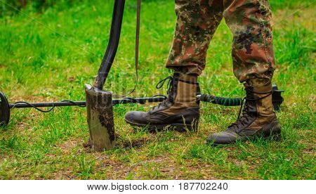 Feet of the tourist in camouflage pants and soldiers' boots against the background of green grass a shovel sticks out in the ground