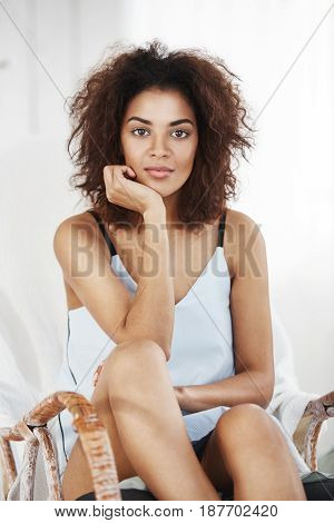 Portrait of young tender beautiful african girl in sleepwear looking at camera sitting resting in chair at home.