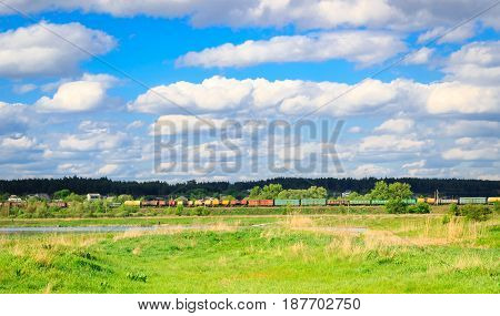 Delightful view of the nature of the endless blue sky and under it rides a long rolling stock with cargo pastures and cisterns around all the green trees grass and lake