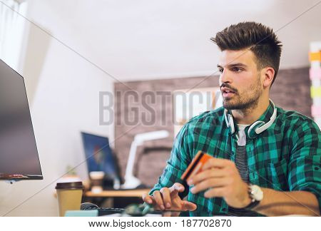 Man paying with credit card on computer at home office