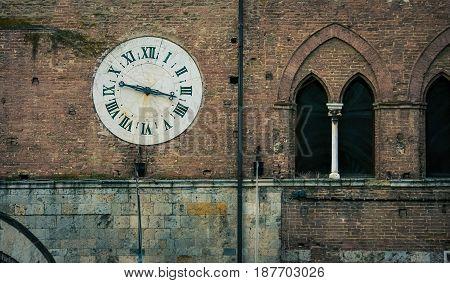 Clock on a brick wall in siena italy