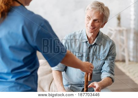 Help me stand up. Handsome tired elderly gentleman sitting on bed and asking the medical worker bringing him his cane for walking
