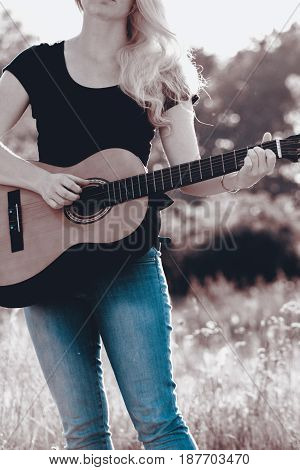 Women play on the spanish guitar. Person play on the music instrument in nature.