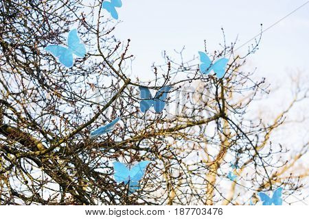 Decoration with spring tree and colorful artificial blue butterflies on blue sky background