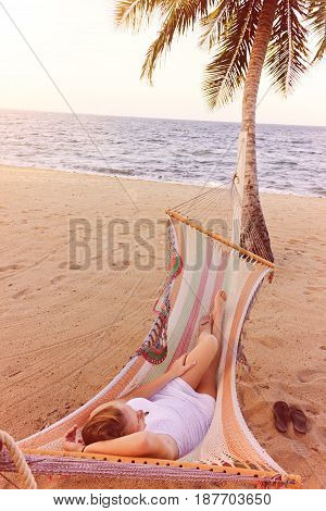 Woman relaxing in a hammock on a beach next to a palm tree