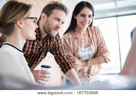 Happy interested workers are helping female employee. Cheerful woman is crossing hands and looking with smile. Man holding cup with non-alcoholic beverage. Low angle