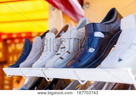 Men's women's and children's summer shoes lie on store shelves
