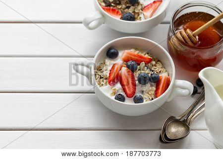 Tasty colorful Breakfast with Oatmeal Yogurt Strawberry Blueberry Honey and Milk on White Wooden Background with Copy Space. Top View.