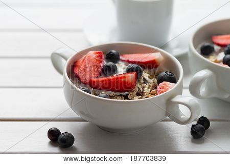 Tasty colorful Breakfast with Oatmeal Yogurt Strawberry Blueberry Honey and Milk on White Wooden Background with Copy Space. Closeup.