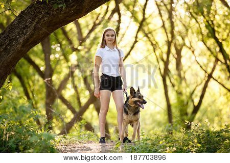Teenage girl in white shirt with her german shepherd dog standing on pathway in the forest
