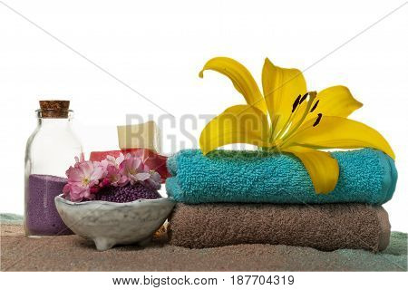 Spa Concept. Closeup of beautiful Spa Products with place for text. Essential oils with beautiful flowers towels spa salt and hand made soap.