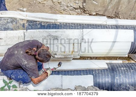 Rigger is affix thermal protection on isolated pipeline gas blowpipe torch heating for melting Styrofoam. poster