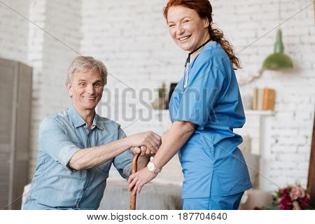 Movements as therapy. Trained experienced positive lady visiting her patient and making sure his recovery going well while suggesting they taking a little walk