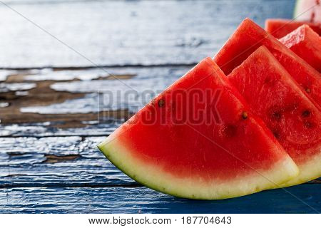 Sliced watermelon closeup. Many slices on an old rustic blue table. Side composition with copy space.