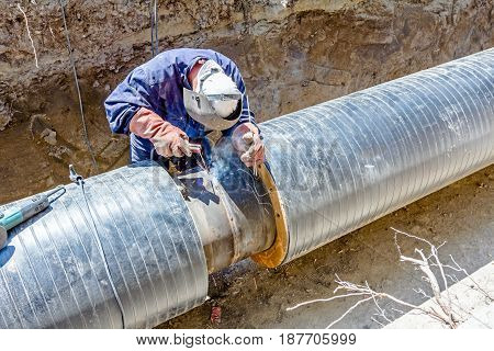 Welder is in trench working hard arc welding pipeline.