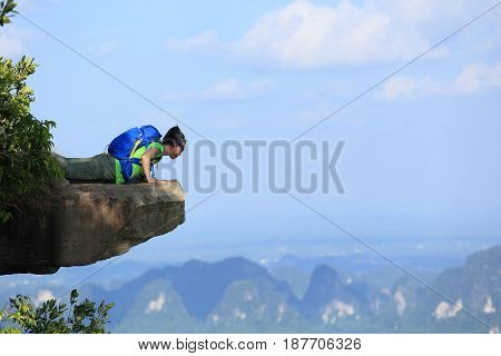successful woman hiker looking down on mountain peak cliff
