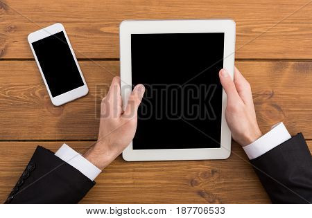 Top view of businessman workplace, hold tablet, copy space. Man working with portable computer and smartphone