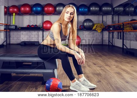 Young girl with blonde hair sitting on board with medicine ball. Fitness healthy lifestyle background