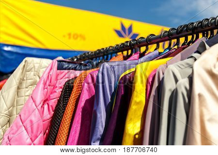 Men's and women's summer clothes sweaters shirts pants t-shirts coat jackets at a discount on the hanger in the shop on the street