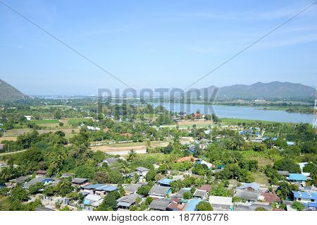 12 January 2017 : Viewpoint from the temple on the mountain to see the scenery of village, river, and mountain at Kanchanaburi province, Thailand