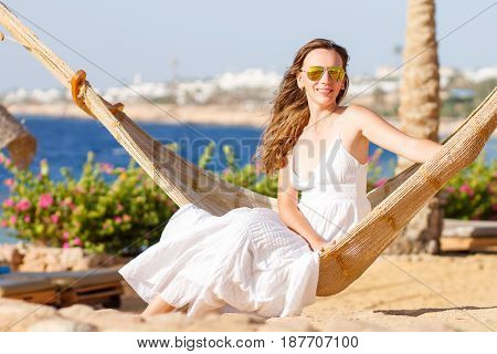 Young beautiful woman in white dress relaxing in hammock near the sea shore. Summer vacation background