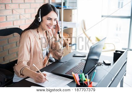 Cheerful female employee is wearing headphone and making notes. She looking at screen of laptop. Portrait