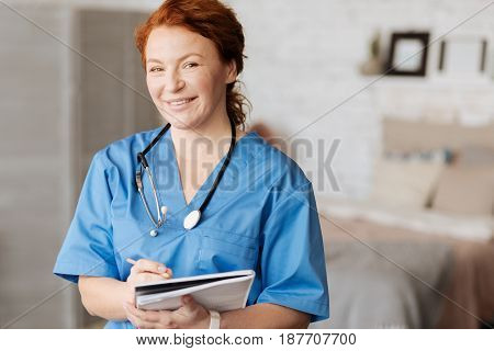 Working in the field. Distinguished wise proficient woman visiting her patient and writing down his symptoms for analyzing them and prescribing treatment